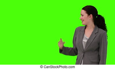 Brunette businesswoman looking at the camera against a green...