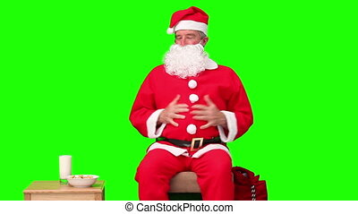 Hungry Santa Claus sitting against a green screen