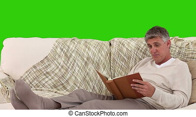 Mature man looking at an album on his sofa - Chroma-key...