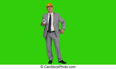 Businessman is working on a building project against a green...