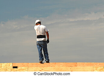 Roofer working on a roof on a hot day - Roofer working on a...