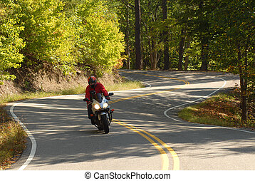 One motorcyclist riding along a winding road - Lone...