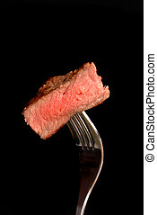A piece of grilled ribeye steak on a fork - Piece of grilled...