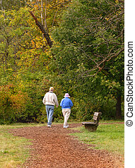 Senior citizen couple walking on path in autumn setting