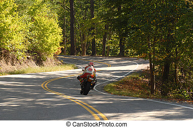 Motorcyclist driving along a winding road - A motorcyclist...