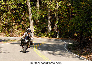 lone motorcyclist riding on a winding forested road - A lone...
