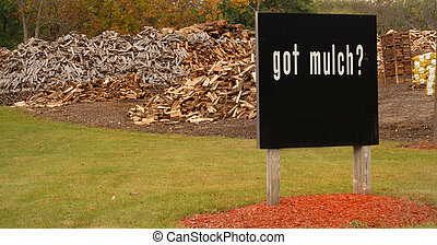 "Sign in front of large wood piles saying ""Got Mulch?"" - A..."