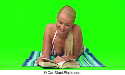 Woman in swimsuit laying down while she is reading a book