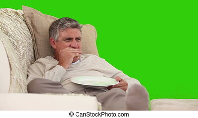 Retired man watching tv while he is eating against a green...