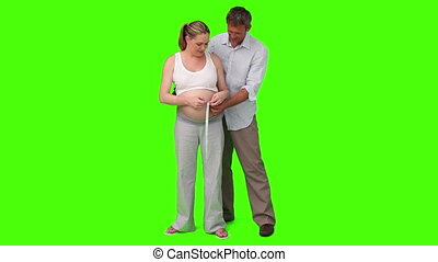 Man measuring the belly of his pregnant woman - Chromakey...