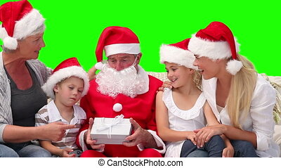 Family on Christmas time with Santa Claus against a green...