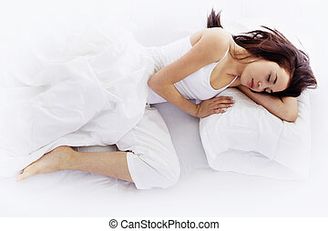 Young woman sleeping on white bed - Stock image of young...