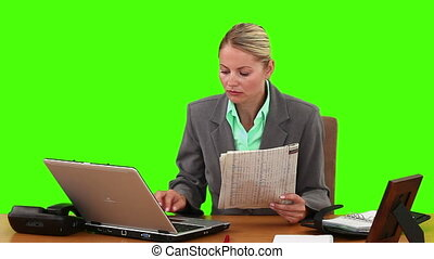 Businesswoman using the newspaper to work against a green...