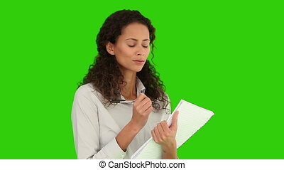 Brunette woman taking note against a green screen