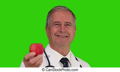 Doctor with his stethoscope showing us an apple against a...