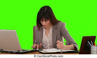 Dark-haired businesswoman calculating her bills at her desk...