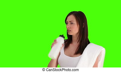 Brunette woman after sport drinking water against a green...