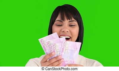 Asian lady showing us her notes against a green screen