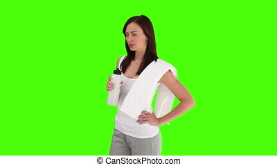 Brunette woman after sport is drinking water against a green...