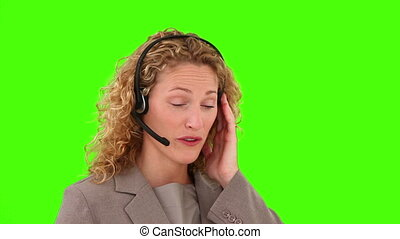 Curly blond haired woman talking on the phone against a...