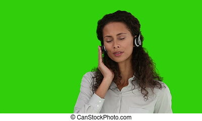 African woman speaking over the headset against a green...