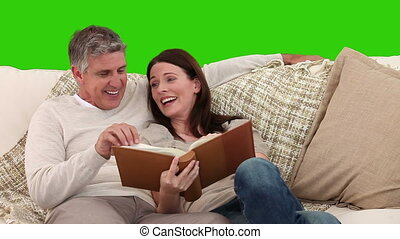 Couple having a lot of fun because they are looking at an album