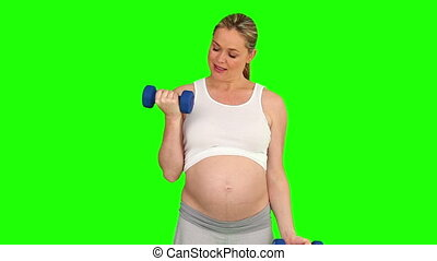 Pregnant woman with dumbbells doing exercise