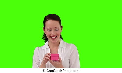 Brunette woman opening a gift against a green screen