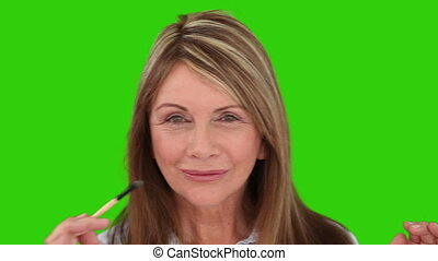 Senior lady putting on make-up against a green screen