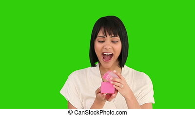 Cute asian woman opening a gift against a green screen