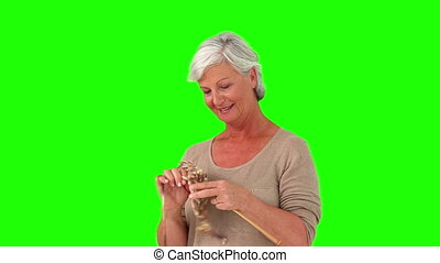 Grandmother knitting very fast against a green screen