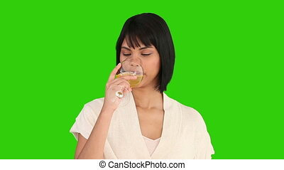 Cute asian woman enjoying a glass of white wine against a...