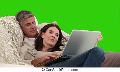 Elderlry couple working on a laptop against a green screen