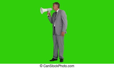 Elderly businessman giving orders through a megaphone...