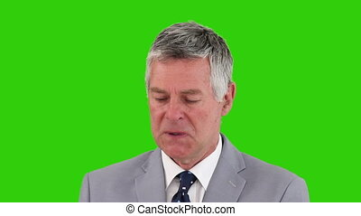 Businessman smelling his cash against a green screen