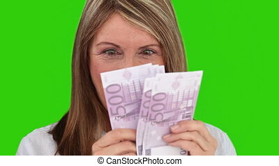 Senior woman counting her cash against a green screen