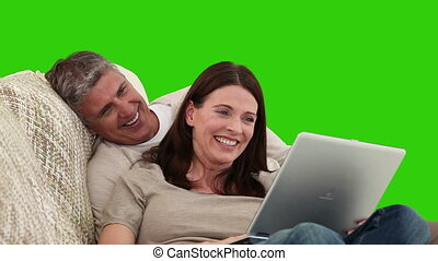 Elderly couple laughing in front of a laptop against a green...