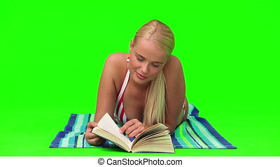 Wonderful blond woman reading a book on the beach