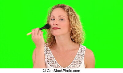 Pretty curly-haired woman putting on make-up against a green...