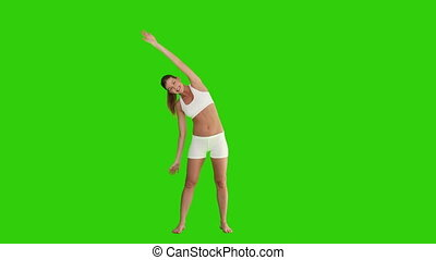 Pretty blond woman doing exercise against a green screen