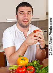 Mid adult man holding apple in kitchen - Serious mid adult...