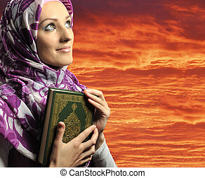 Adorable Muslim girl holding holy book Koran, against red sky