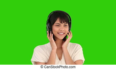 Cute asian woman listening to music with an headphones -...