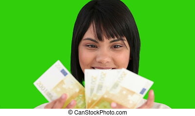 A young pretty asian woman counting her cash against a green...