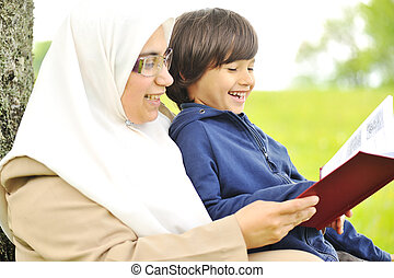 Mother Muslim and her son in the nature, reading together