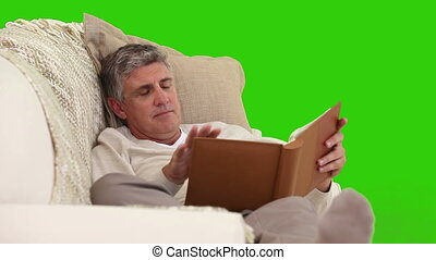 Retired man looking at an album on his sofa against a green...