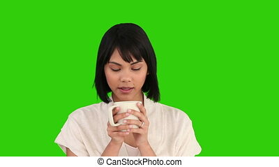 Asian woman drinking a cup of tea against a green screen