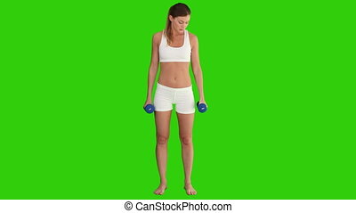 Pretty woman in sportswear with dumbbells against a green...