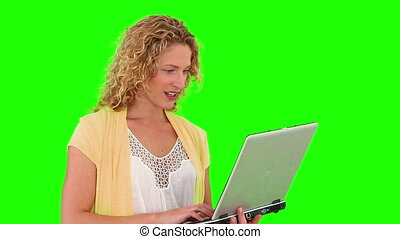 Curly blond haired woman using a laptop