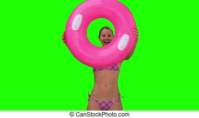 Blond woman in a pink swimsuit playing with a rubber ring